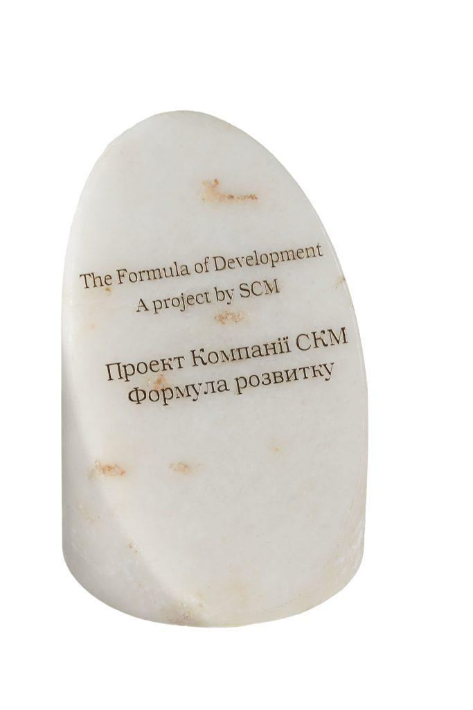 Золотой логотип на каменной награде